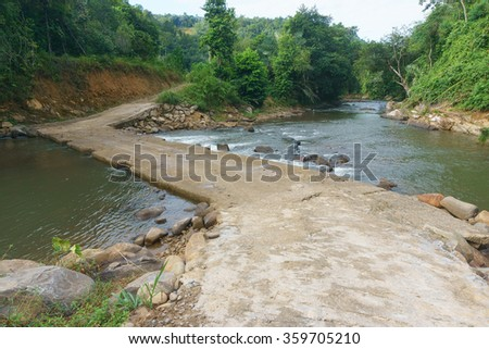 Typical rural road in Sabah Borneo with concrete river crossing using culvert.A part of road crossing river in the jungle of Sabah Malaysian Borneo.