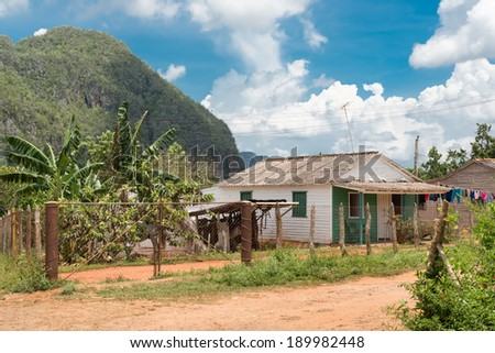 Typical rustic wooden house at the Vinales Valley in Cuba with the mountains just behind the house - stock photo
