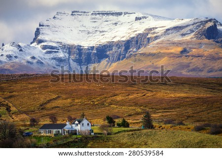Typical Scottish landscape with farmhouse and a spectacular snow-capped ridge in the background - stock photo