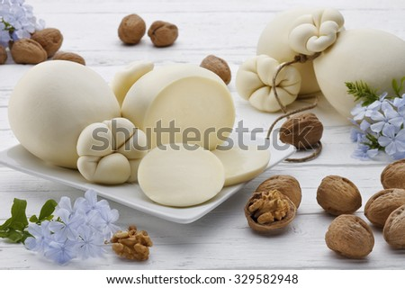 Typical sicilian cheese called provola on a white dish with flowers and walnuts on a white wooden table. - stock photo