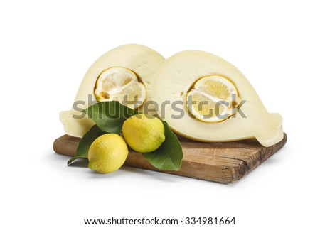 Typical sicilian cheese called provola sliced with lemon inside, with lemons on a wooden cutting board on white background - stock photo