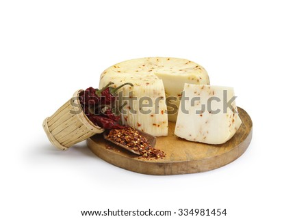 Typical Sicilian chili cheese from sheep, with a basket of chili on a wooden cutting board. On white background - stock photo