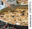 Typical spanish paella for a hundred persons - stock photo