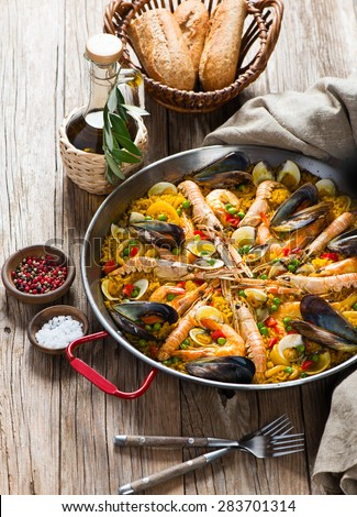 Typical spanish seafood paella in traditional pan on a rustic wooden background - stock photo
