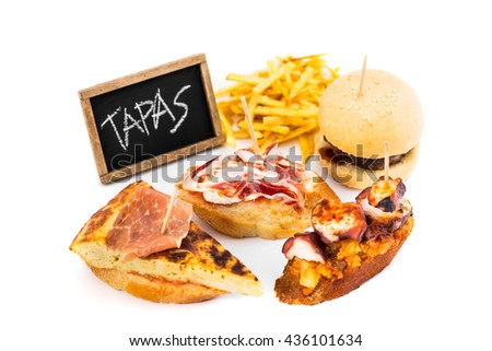 Typical spanish tapas with chalkboard isolated on white background. - stock photo