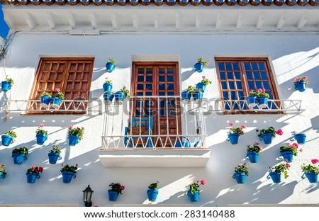 Typical spanish white village. Whitewashed building with blue flower pots in facades. Rancho Domingo, Benalmadena town. Malaga. Costa del Sol. Southern Spain - stock photo