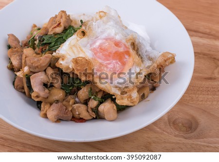 Typical street food in Thailand (Pad Kra Prao); Stired fried chicken with holy basil and fried runny egg yolk on steamed jasmine rice on wooden background.
