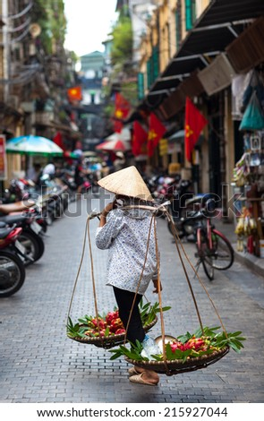 Typical street vendor with palm-leaf conical hat in Hanoi, Vietnam, they sell foods around ancient town. - stock photo