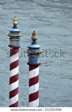 Typical striped poles for mooring boats in Venice. Italy - stock photo