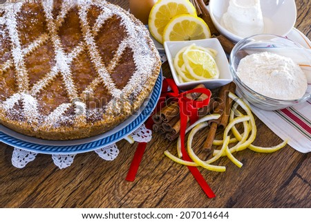 Typical sweet Campania - Neapolitan pastiera on wooden table with ingredients - stock photo