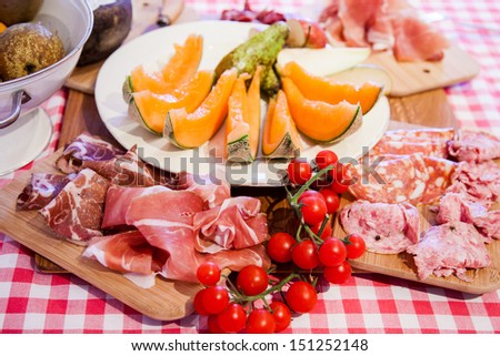 Typical Tuscany cuisine with prosciutto, cheese and fruit. - stock photo