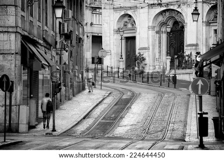 Typical view in black and white of the streets of Lisbon, capital of Portugal, steeply going up, early morning, still empty, with the rails for the tramway 28 idle lying in the stones - stock photo