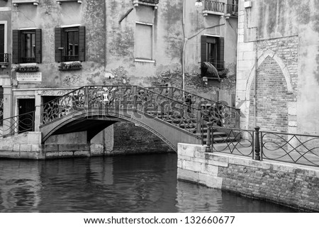 Typical view in black and white on old houses in Venice, along a canal and a bridge visible part of the image