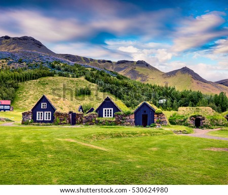 Typical view of Icelandic turf-top houses. Colorful summer morning in the Skogar village, south Iceland, Europe. Artistic style post processed photo.