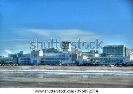 Typical view of international airport outdoors with an air traffic control tower  on a clear blue sky - stock photo