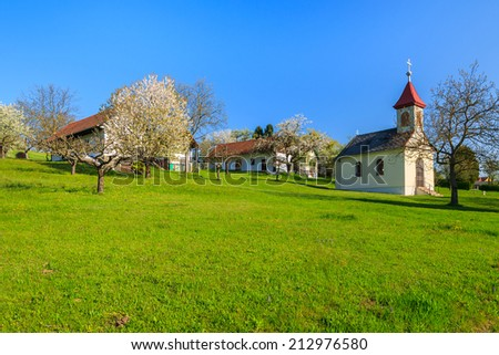 Typical village with church building on green field in rural landscape, Hamerlberg in Burgenland, Austria  - stock photo