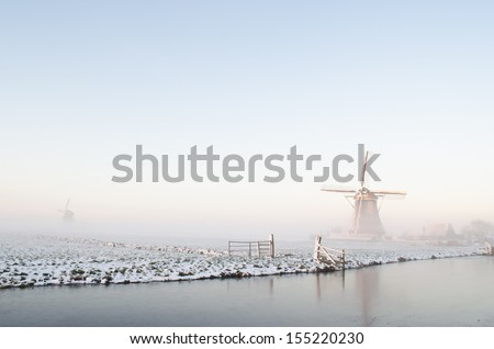 Typical winter landscape in Holland (the Netherlands) with a windmill, a canal, snow, ice and fog. - stock photo