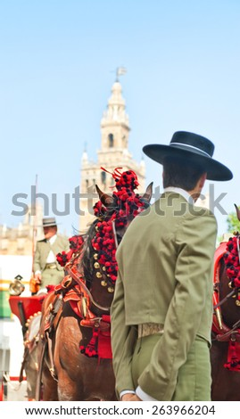 typicall image on Seville the Cathedral, La Giralda, horse and carriage and men with hats - stock photo