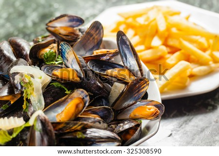 Typically Belgian dish: steamed mussels and french fries - stock photo