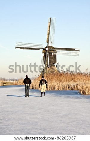 Typically dutch: ice skating on a frozen canal  with view on a windmill on a cold winterday in the Netherlands - stock photo