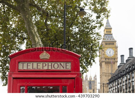 typically english red phone booth in london with the Big Ben in the background - stock photo
