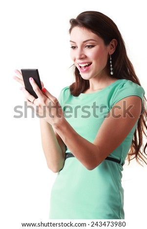 Typing a message to you. Beautiful women holding the mobile phone and smiling while standing against white background  - stock photo