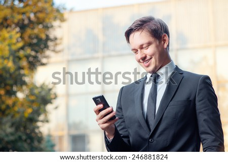 Typing business message. Cheerful young man in formal wear holding mobile phone and smiling while standing outdoors - stock photo