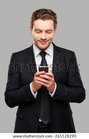 Typing business message. Confident young man in formalwear holding mobile phone and smiling while standing against grey background - stock photo