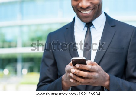 Typing business message. Cropped image of cheerful young African man in formal wear holding mobile phone and smiling while standing outdoors - stock photo