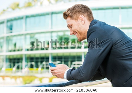 Typing business message. Side view of handsome young man in formalwear holding mobile phone and looking at it with smile while standing outdoors - stock photo