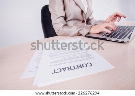 Typing Contract. Businessman sitting at the table and typing a business plan on a laptop while businessman sitting at desk on isolated gray background - stock photo