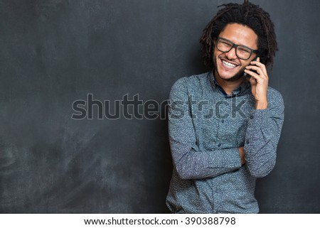 Typing message. Handsome young man with afro hair in shirt holding mobile phone