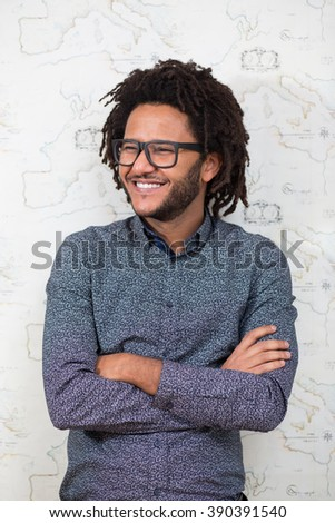 Typing message. Handsome young man with afro hair in shirt holding mobile phone - stock photo