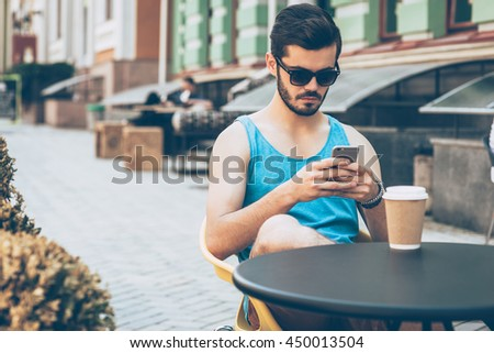 Typing message to friend. Confident young man in casual wear holding smart phone and looking at it while sitting at sidewalk cafe outdoors  - stock photo