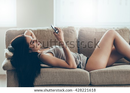 Typing message to him. Beautiful young woman in panties and tank top holding smart phone and looking at it with smile while lying on couch at home - stock photo