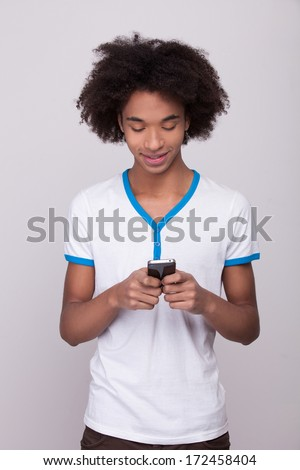Typing messages to friends. Cheerful African teenager holding mobile phone and looking at it while standing isolated on grey background - stock photo
