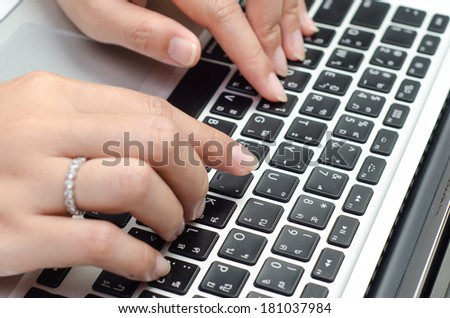 Typing on keyboard. Close up of female finger