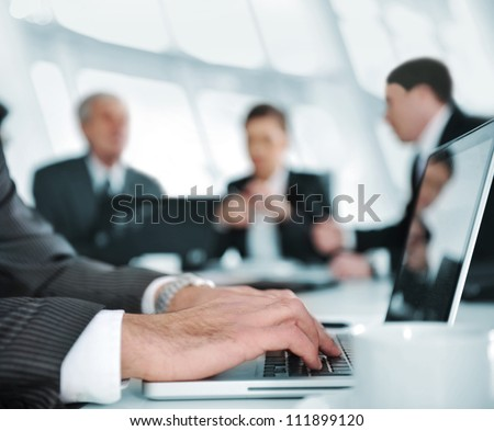 Typing on laptop while the business group having meeting - stock photo