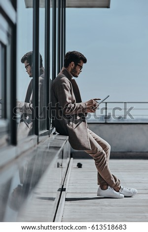 Typing quick message.  Full length of young man using digital tablet while leaning on the office building outdoors