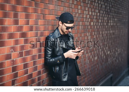 Typing text message. handsome young man in smart casual wear holding mobile phone while leaning at the brick wall - stock photo