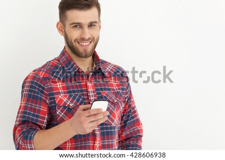 Typing text message.Portrait of handsome young man in casual wear holding mobile phone against white wall. - stock photo