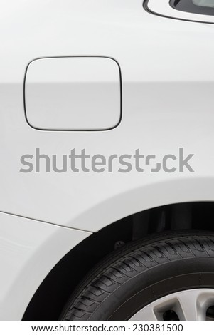 tyre and petrol cap cover and window of a white car - stock photo