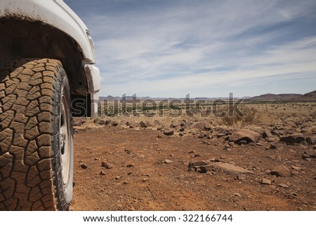 tyre of a off road car in the red sand of the Kalahari desert, Namibia, Africa - stock photo