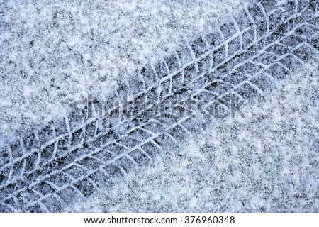 Tyre tracks in snow - driving in winter weather - stock photo