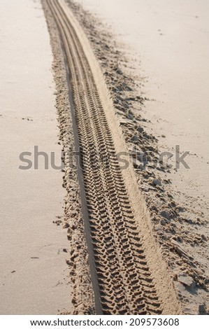 tyre tracks on the sand of the beach - stock photo