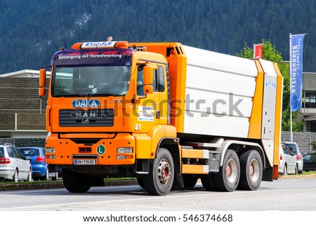 TYROL, AUSTRIA - JULY 29, 2014: Orange garbage truck MAN TGA 26.350 in the town street.