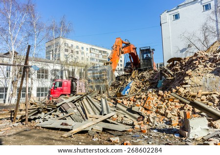 Tyumen, Russia - April 6, 2015: Destroyed two-storeyed barrack at address Holodilnaya street 88. Excavator works on loading of construction garbage from demolished house into truck - stock photo