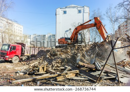Tyumen, Russia - April 6, 2015: Destroyed two-storeyed barrack at address Holodilnaya street 88. Excavator loads construction garbage from demolished house into truck - stock photo