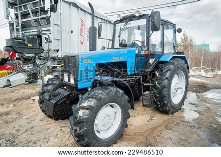"Tyumen, Russia - April 04. 2014: IV Tyumen specialized exhibition ""Agricultural Machinery and Equipment"". Tractor demonstration of Belarus production on platform open-air - stock photo"