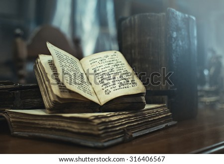 TYUMEN, RUSSIA - AUGUST 24, 2015: Antique hardcover books of 16th Century A.D. with Old Slavonic religious texts lying on a table in the Tyumen State University Library and Learning Center.